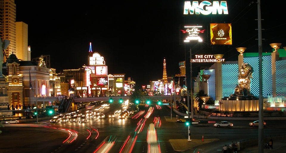 A late night street view of the Las Vegas Strip, with car lights and resort signs shining.