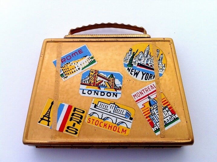 A vintage suitcase with travel stickers from across the world.