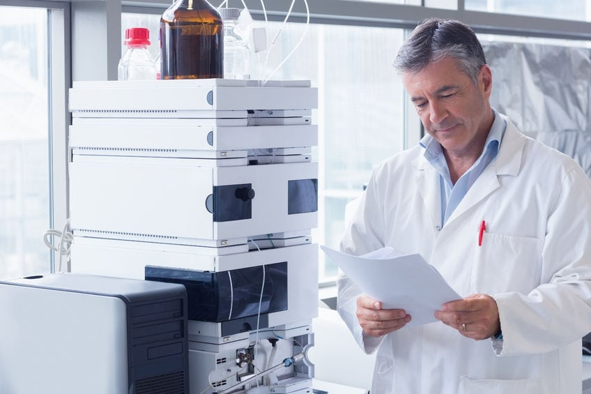 A scientist standing in a lab coat reads an analysis in a laboratory