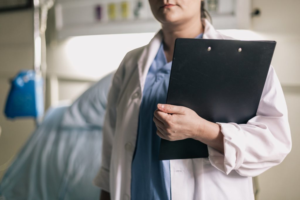 female medical professional-holds-clipboard in hospital room photo